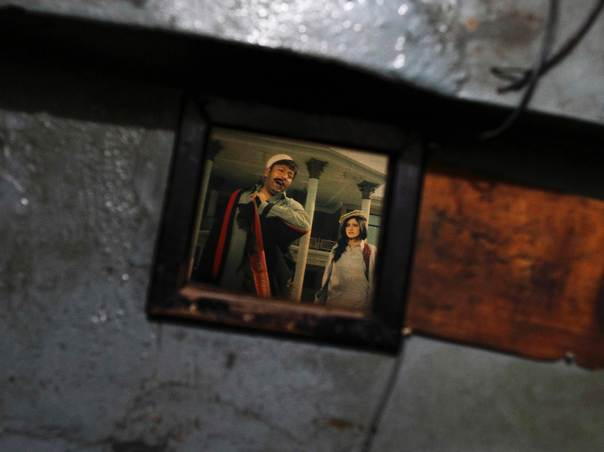 A scene of an old Pashto movie is seen through a window at Arshad ...
