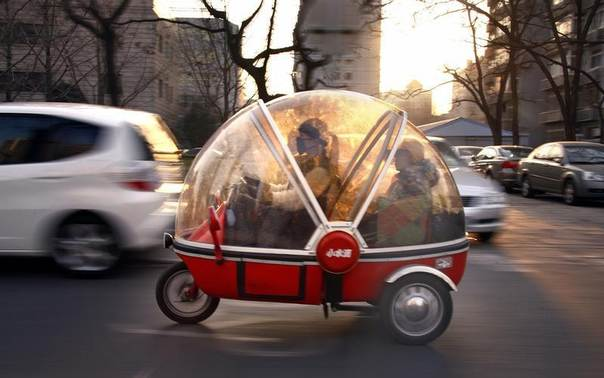 A woman and her son sit inside the capsule of an electric tricycle as they drive along a main road in central Beijing, March 15, 2012. REUTERS/David Gray