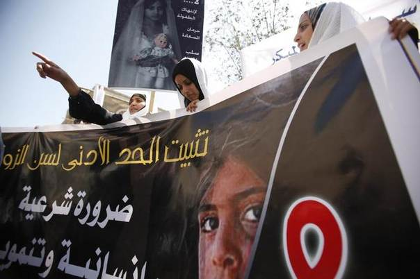 Yemeni women hold up a poster portraying a child bride during a sit-in outside the parliament in Sanaa March 23, 2010.  REUTERS/Khaled Abdullah