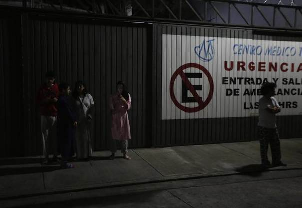 People wait outside their houses after an earthquake struck Mexico, in Mexico City July 29, 2014. REUTERS/Henry Romero
