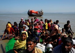 Rohingya refugees sit on a makeshift boat as they get interrogated by the Border Guard Bangladesh near Cox's Bazar