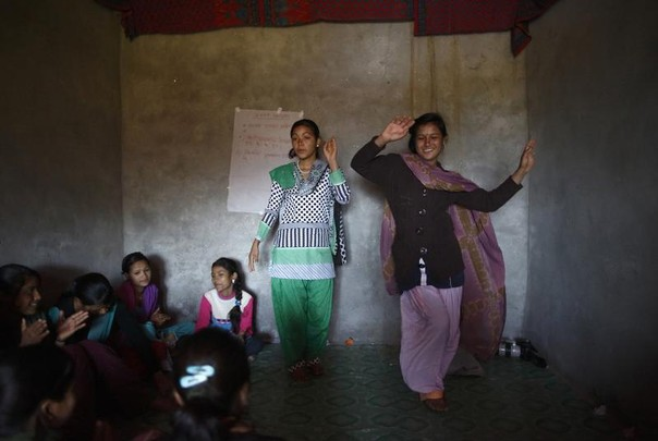 Sanu Bhul, 15, (C) and Nirmla Kadayat, 16, dance to a song about Chaupadi during an awareness class at Bailpata village in Achham District in western Nepal February 17, 2014. REUTERS/Navesh Chitrakar