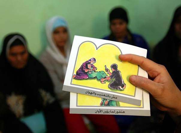 A counsellor holds up cards used to educate women about female genital mutilation (FGM) in Minia, Egypt, June 13, 2006. Stringer/REUTERS