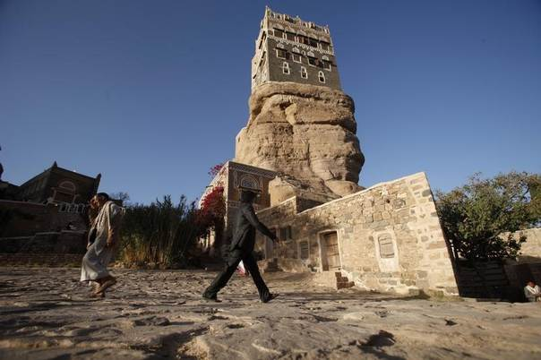 People walk past Dar al-Hajar (Rock Palace), one of Yemen's most famous monuments, standing atop a rock hill in a valley 15 km (9 miles) northwest of capital Sanaa, October 16, 2013. REUTERS/Khaled Abdullah
