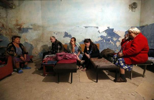 Local residents sit inside a bomb shelter where they are seeking refuge during what they say is shelling in Donetsk, Ukraine, August 9, 2014. REUTERS/Sergei Karpukhin