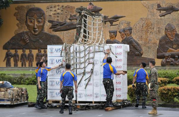A U.S. Marine stands on top of boxes containing tent material from USAID, as he and Philippine soldiers prepare the load to be deployed by a U.S. military airlift to victims of super typhoon Haiyan, at Manila airport, on Nov. 13, 2013. REUTERS/Wolfgang Rattay