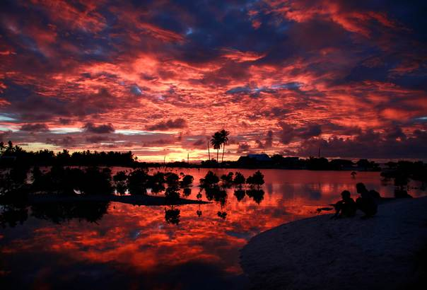 Villagers watch the sunset over a small lagoon near the village of Tangintebu on South Tarawa in the central Pacific island nation of Kiribati on May 25, 2013. REUTERS/David Gray