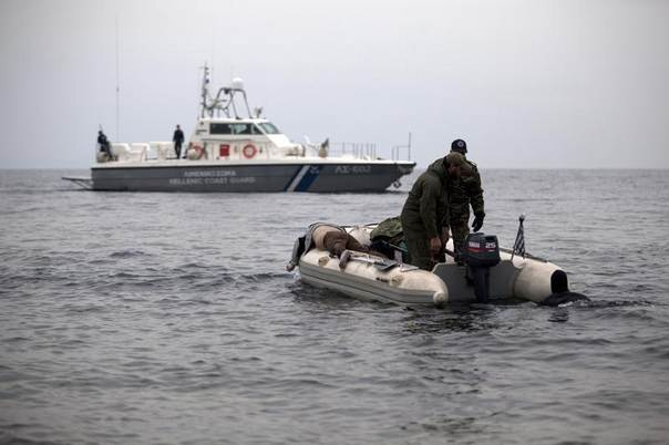This photo from December 2012 shows reservist Greek army commandos and Coast Guard officers carrying the body of an immigrant on a dingy off the island of Lesvos after a small boat carrying migrants hoping to get to Greece sank near the eastern island, drowning at least 20 people. REUTERS/Giorgos Moutafis