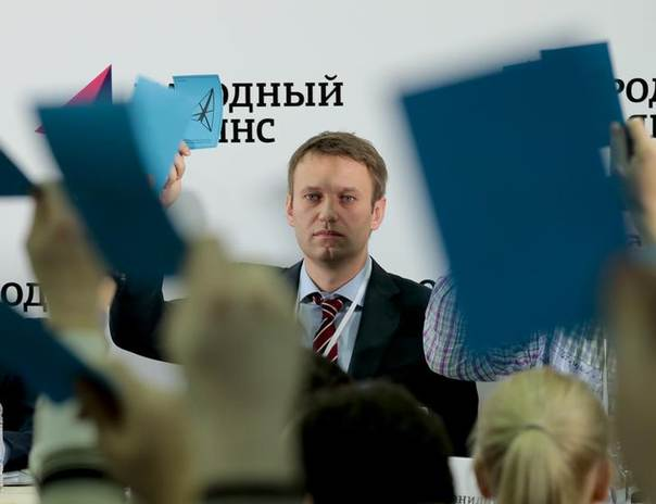 Russian opposition leader Alexei Navalny holds his membership card during voting at a congress of the People's Alliance political party in Moscow November 17, 2013. Message on background reads