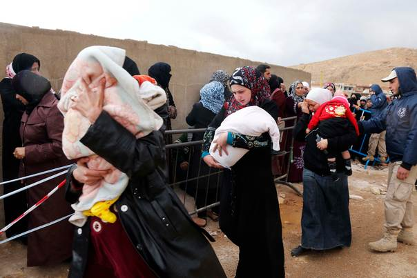 Syrian women, fleeing the violence from the Syrian town of Qara, carry their babies as they queue to register to get help from relief agencies at the Lebanese border town of Arsal, in the eastern Bekaa Valley November 18, 2013. REUTERS/Mohamed Azakir
