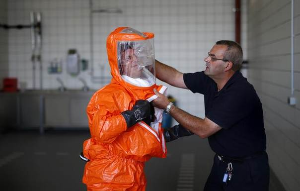 A fire brigade paramedic is assisted while putting on a sealed protective suit during a drill for the crew of a special ambulance, in Frankfurt August 21, 2014. REUTERS/Kai Pfaffenbach