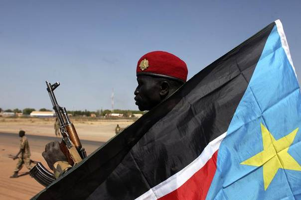 An SPLA soldier is pictured behind a South Sudan flag as he sits on the back of a pick-up truck in Bentiu, Unity state January 12, 2014. REUTERS/Andreea Campeanu
