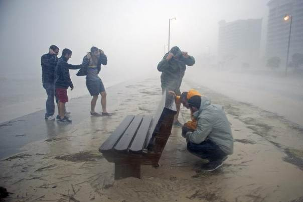 Kyle Taylor and his father Robert Taylor (R) seek shelter behind a bench along Beach Blvd. as Hurricane Isaac passes through Gulfport, Mississippi, United States, August 29, 2012. REUTERS/Michael Spooneybarger