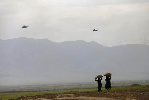 Military helicopters fly as children walk on the outskirts of Kabul, Afghanistan, May 1, 2014. REUTERS/Mohammad Ismail