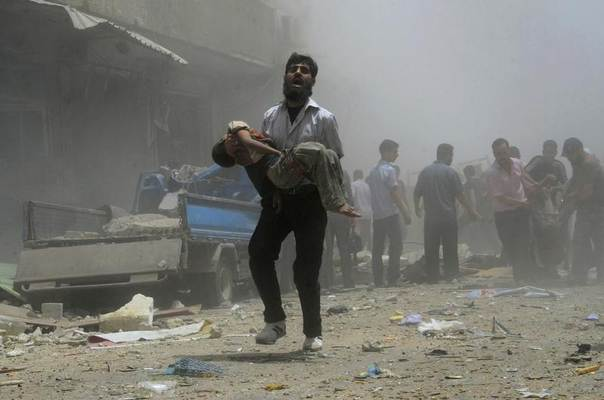 A resident carries a wounded child injured by what activists claim was a car explosion in central Douma, eastern al-Ghouta, near Damascus, Syria, July 19, 2014. REUTERS/Yousef Albostany