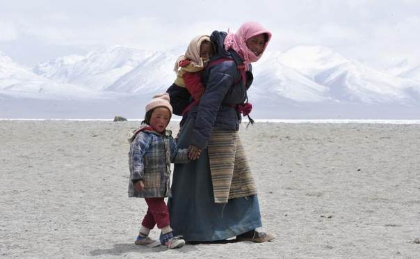 A Tibetan woman walks with her children near Lake Namtso, Tibet Autonomous Region, May 11, 2011. REUTERS/Stringer