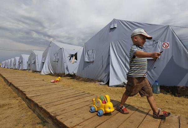 Alexander, 4, walks with a toy at a temporary tent camp set up for Ukrainian refugees outside Donetsk, located in Russia's Rostov region near the Russian-Ukrainian border, August 18, 2014. REUTERS/Alexander Demianchuk