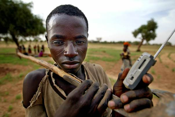 A farmer listens to his transistor radio as he returns home from work near the village of Koumboula in southern Niger on June 30, 2005. REUTERS