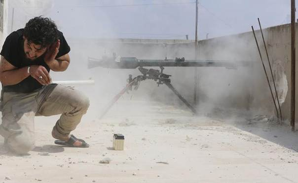 A Free Syrian Army fighter reacts as he fires his weapon towards forces loyal to Syria's President Bashar al-Assad in the town of Morek in Hama province April 4, 2014. REUTERS/Badi Klif