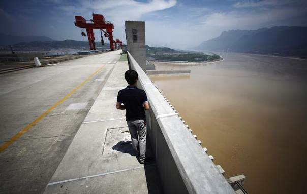 A man stands on the Three Gorges dam in Yichang, Hubei province, China, August 9, 2012. REUTERS/Carlos Barria