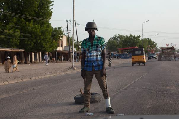 A civilian joint task force member stands guard at a checkpoint in Maiduguri, on May 22, 2014. Civilian joint task force are government-sponsored civilian self-defence and community-policing groups within Borno state that some locals said have brought security to Maiduguri, according to local government officials. REUTERS/Joe Penney