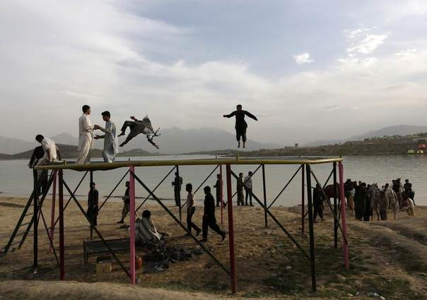 Afghans play on a trampoline along Qargha Lake, on the outskirts of Kabul April 28, 2014. REUTERS/Mohammad Ismail