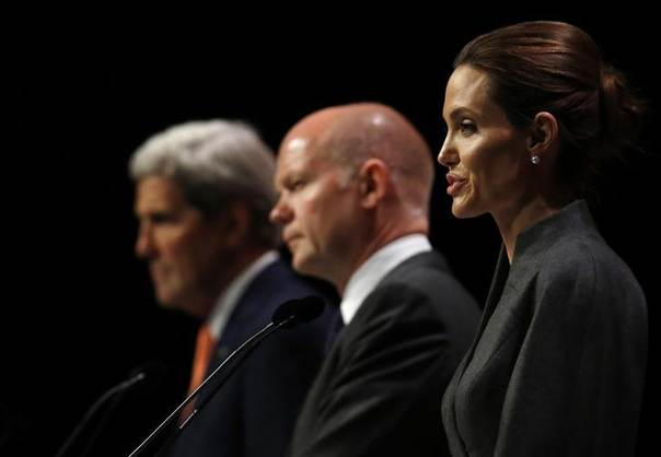 Actress and campaigner Angelina Jolie speaks alongside U.S. Secretary of State John Kerry (L) and Britain's Foreign Secretary William Hague at a summit to end sexual violence in conflict, at the Excel centre in London June 13, 2014. REUTERS/Luke MacGregor