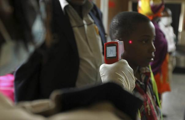 A boy's temperature is taken using an infrared digital laser thermometer at the Nnamdi Azikiwe International Airport in Abuja,  Nigeria, August 11, 2014. REUTERS/Afolabi Sotunde