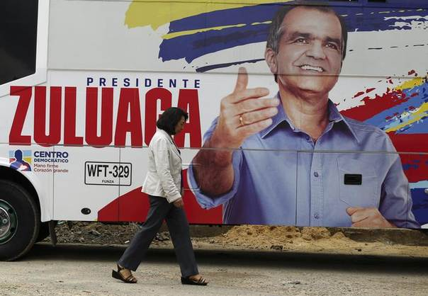 A woman walks past a banner on Colombian presidential candidate Oscar Ivan Zuluaga's campaign bus, at an election rally in the Bogota neighborhood of Suba May 6, 2014 REUTERS/John Vizcaino