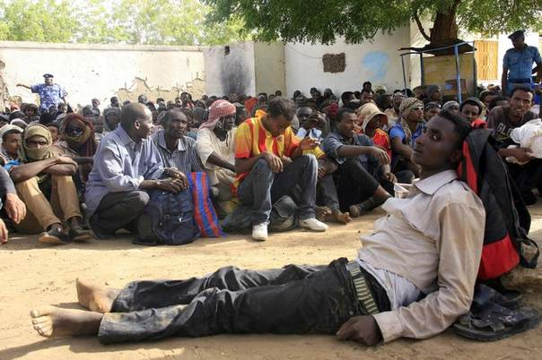 Illegal immigrants who were abandoned by traffickers in a remote desert area wait inside a military base in Dongola town, after being located by Sudanese and Libyan forces, May 3, 2014.  REUTERS/Stringer