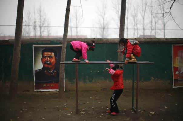 Students play next to a portrait of Soviet leader Joseph Stalin at the Democracy Elementary and Middle School in Sitong town, Henan province December 3, 2013. REUTERS/Carlos Barria