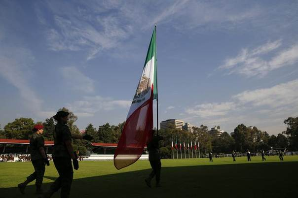 Members of Mexico's honor guard march with the Mexican flag during an official reception for U.S. Defense Secretary Chuck Hagel and Canada's Defense Minister Rob Nicholson in Mexico City April 24, 2014. REUTERS/Shannon Stapleton