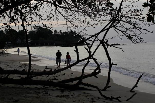 People walk along the beach in the Seychelles on February 29, 2012. REUTERS/Ahmed Jadallah