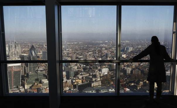 A woman looks out at London's financial district from a window in The View gallery at the Shard, western Europe's tallest building. January 9, 2013. REUTERS/Luke Macgregor