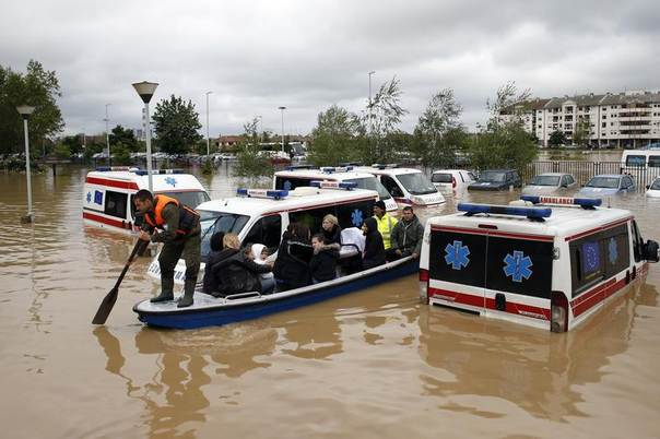 A Serbian rows a boat past flooded ambulance vehicles in the flooded town of Obrenovac, southwest of Belgrade, Serbia, May 17, 2014. REUTERS/Marko Djurica