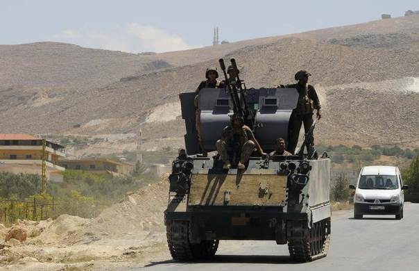 Lebanese army soldiers sit atop of an armoured carrier at the entrance of the Sunni Muslim border town of Arsal, in eastern Bekaa Valley, August 5, 2014. REUTERS/Hassan Abdallah
