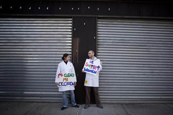 Two pro-abortion rights protesters await the arrival of other anti-abortion protesters outside the Choices Women's Medical Center in Queens, New York October 20, 2012. REUTERS/Andrew Kelly