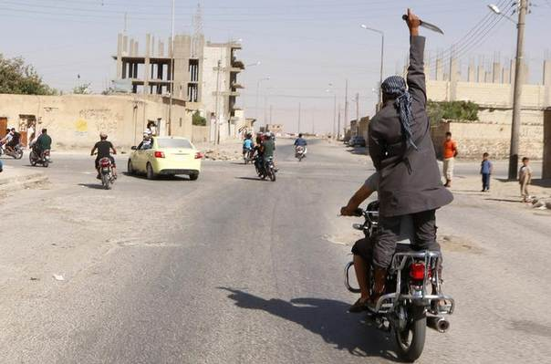 A man holds up a knife as he rides on the back of a motorcycle touring the streets of Tabqa city with others in celebration after Islamic State militants took over Tabqa air base, in nearby Raqqa city August 24, 2014. REUTERS/Stringer