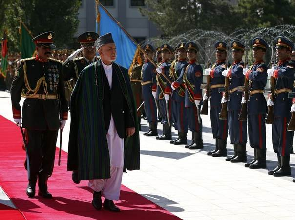 Afghanistan's President Hamid Karzai (C) inspects the honour guard after Eid al-Fitr prayers to mark the end of Ramadan, at the presidential palace in Kabul, Afghanistan, July 28, 2014. REUTERS/Omar Sobhani