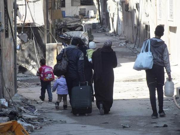 Civilians carry their belongings as they walk towards a meeting point to be evacuated from a besieged area of Homs February 9, 2014. REUTERS/Yazan Homsy