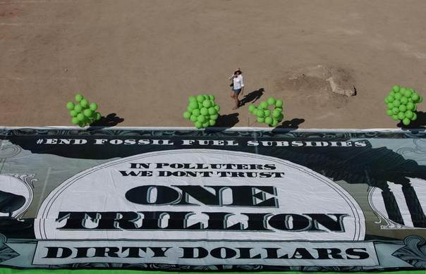 An activist walks past a banner of a giant 1 trillion dollar bill, representing the amount in taxpayer dollars spent yearly by governments on fossil fuel subsidies, in Los Cabos, June 18, 2012. REUTERS/Victor Ruiz Garcia