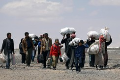 Internally displaced people who fled Raqqa city carry their belongings as they leave a camp