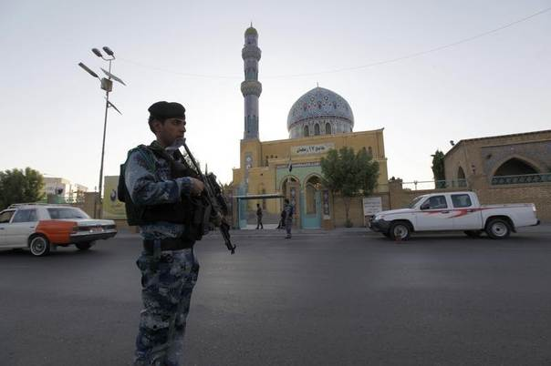 An armed Iraqi policeman stands guard outside a Sunni mosque during Eid al-Fitr prayers in Baghdad, Iraq, July 28, 2014. REUTERS/Ahmed Saad