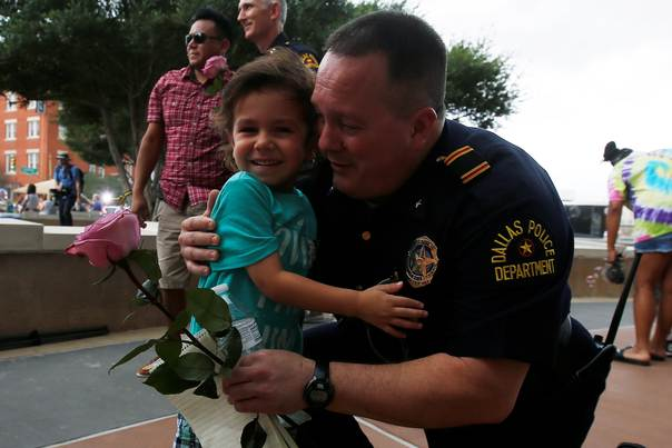 A child hugs a Dallas police officer at Dallas Police