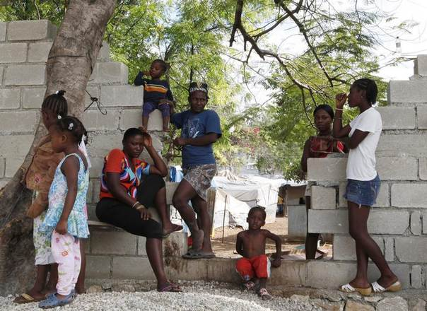 Haitians made made homeless by the 2010 earthquake stand in an opening in the wall being built by the owners of the land occupied by Shelter Camp 3, one of 385 informal 'tent cities' still existing since the disaster, in the Delmas suburb of Port-au-Prince, April 22, 2013. REUTERS/Marie Arago