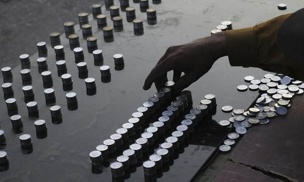 A money changer counts Pakistani coins at his makeshift booth near a bus stop in Karachi March 20, 2012. REUTERS/Athar Hussain