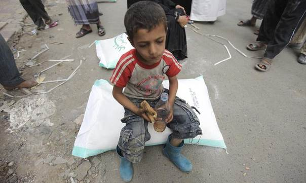 A boy eats while receiving aid from the Red Crescent Society in Sanaa July 2, 2012. REUTERS/Mohamed al-Sayaghi
