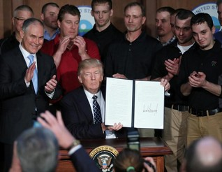 "U.S. President Donald Trump holds up an executive order on ""energy independence,"" eliminating Obama-era climate change regulations"
