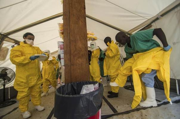 Medical staff working with Medecins sans Frontieres (MSF) put on their protective gear before entering an isolation area at the MSF Ebola treatment centre in Kailahun July 20, 2014. Sierra Leone now has the highest number of Ebola cases, at 454, surpassing neighbouring Guinea where the outbreak originated in February. Picture taken July 20, 2014. REUTERS/Tommy Trenchard
