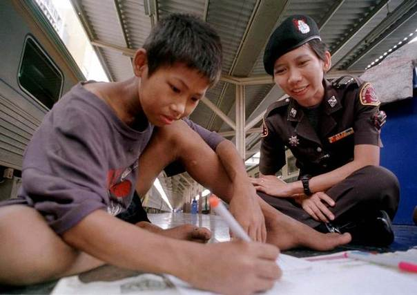 A Thai railway police woman teaches a street child boy how to write at Hualampong Railway Station in central Bangkok. REUTERS/Stringer